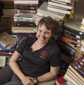 PA staff Kate Post has her portrait taken in the midst of 1000 books as part of the new faculty portraits photographed in the studio on Wednesday, August 16, 2017 in Chico, Calif.
